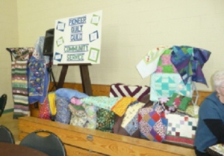 Nice display of Community Service quilts, pillowcases, and Necessities pillows.